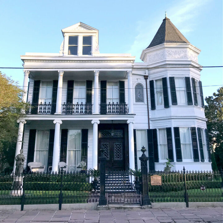 The exterior of a large white house in the Garden District.