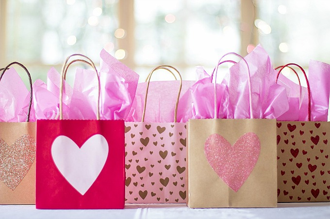 A row of gift bags filled with pink paper.