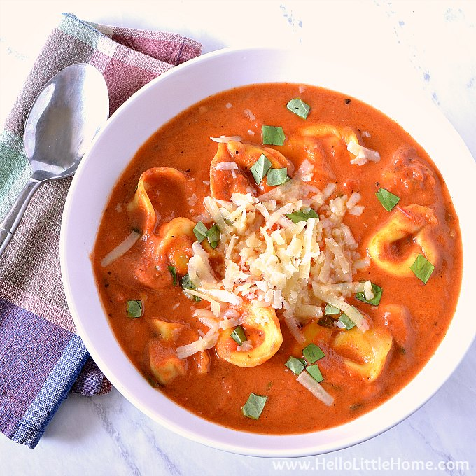 A bowl of creamy tomato tortellini soup on a marble counter.