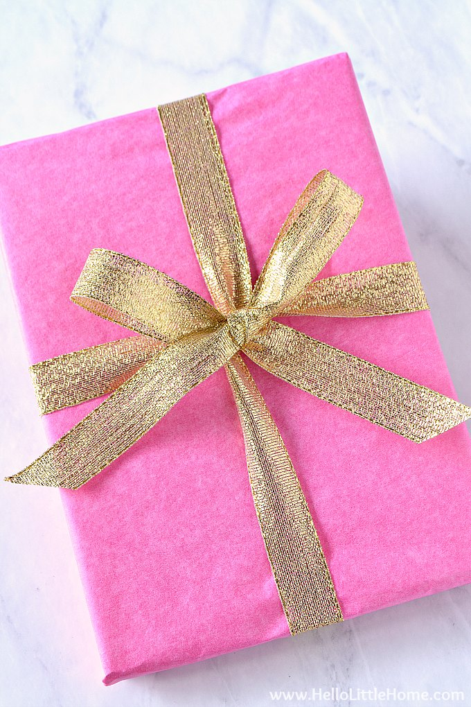 A simple ribbon bow in gold on a pink package.