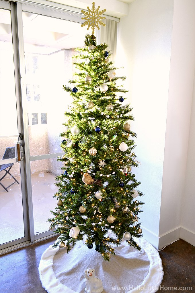 A Tall, Narrow Modern Christmas Tree with Blue, Gold, and White Ornaments