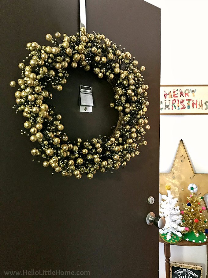 Open Door with Gold Wreath and Merry Christmas Sign in Background