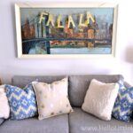 Modern Christmas Decorating Ideas: Couch Decorated with Fur and Blue Pillows, Large Painting Decorated with Fa La La Banner