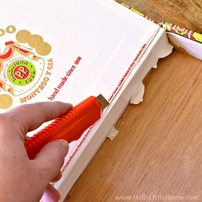 Removing the lid from the cigar box with a utility knife.