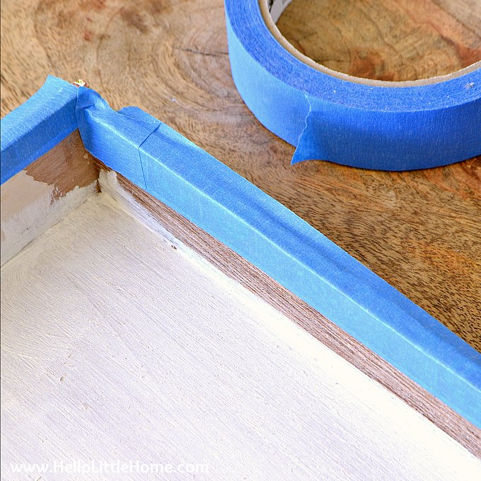 Applying painters tape to protect the inside of the cigar box frame.
