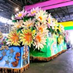 Huge Mardi Gras Float decorated with colorful flowers.