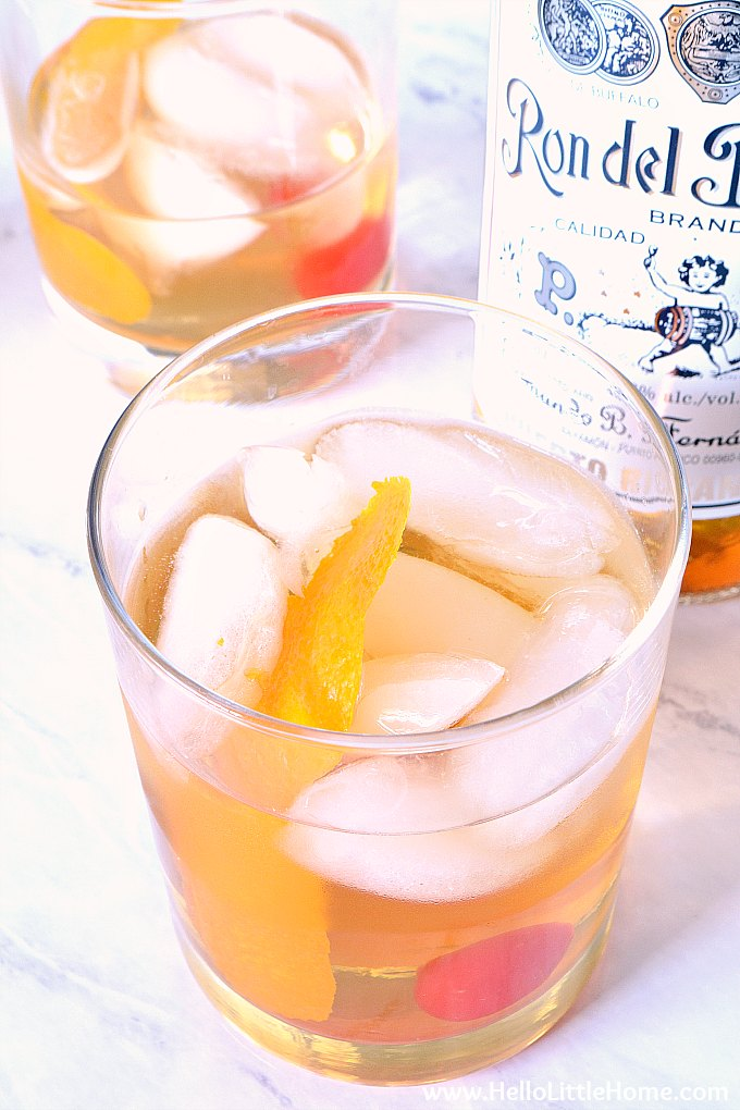 Two Rum Old Fashioneds, garnished with Orange and Maraschino Cherries.