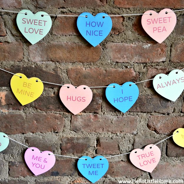 Valentin's Day Conversation Heart Banner made with free printables hanging on a brick wall.