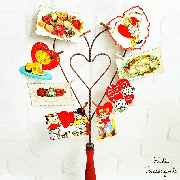 A cute vintage Valentine's Day decor idea: a heart-shaped rug beater covered with vintage Valentines.