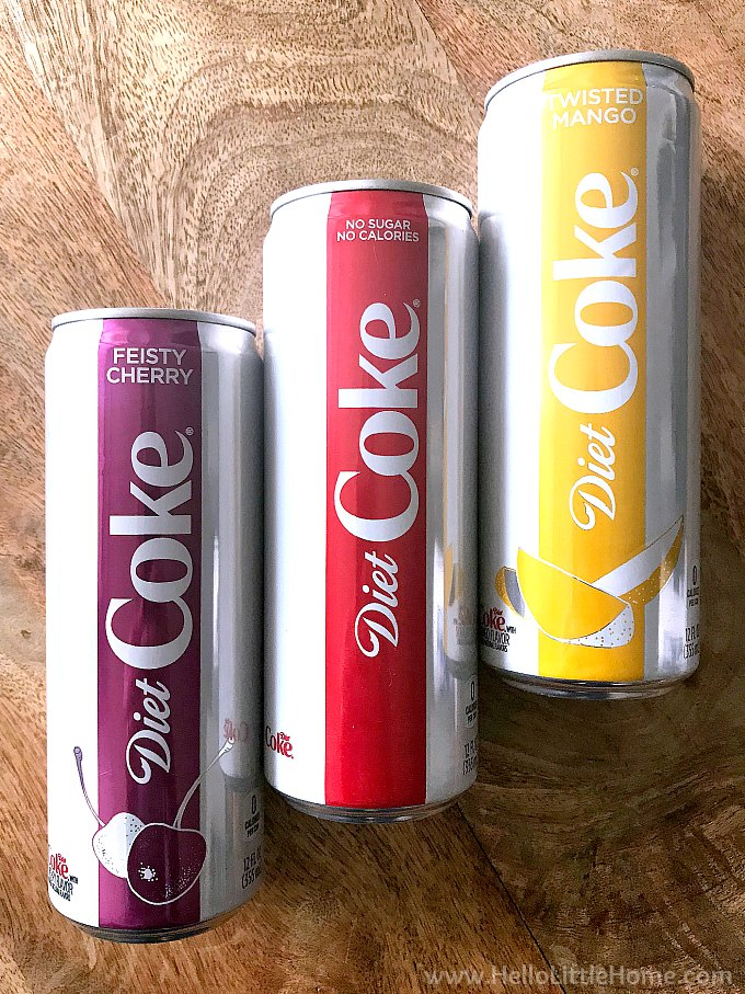 Three cans of Diet Coke on a wood table.
