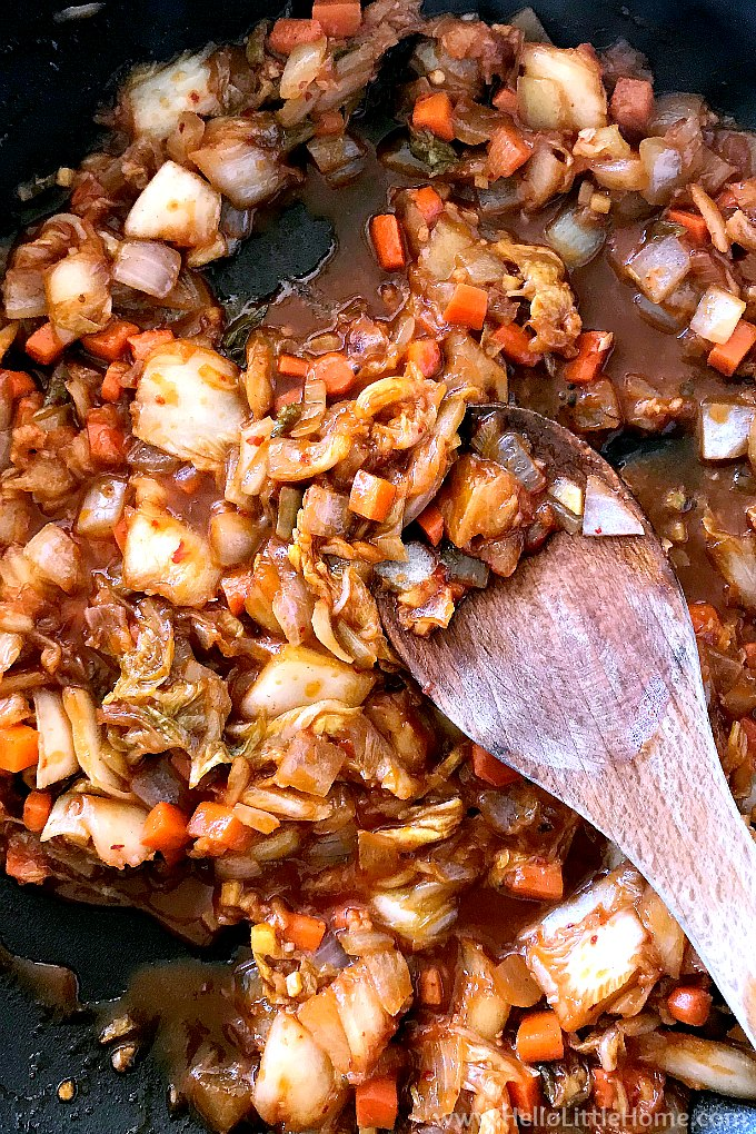 Stir frying kimchi and other ingredients in a pan with a wood spoon.