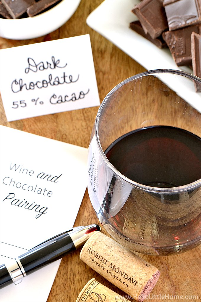 Closeup of a glass of red wine, wine corks, and a wine and chocolate pairing card.
