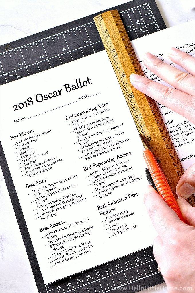 Cutting the free printable 2018 Oscar Ballots in half with a utility knife.