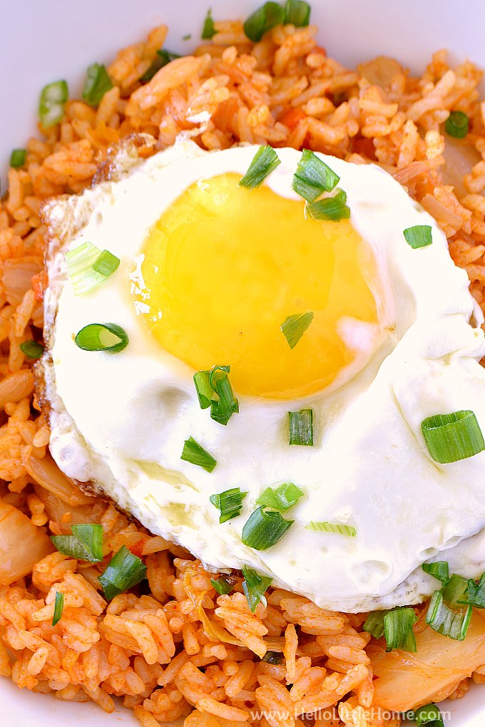 Closeup of a bowl of vegetarian Korean fried rice topped with a fried egg and green onions.