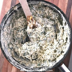 Mixing pepper jack cheese in Mexican Baked Spinach Dip.