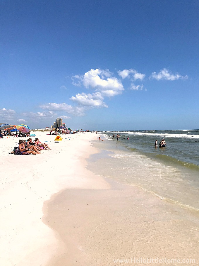 People lounging on the beach and in the water at Gulf State Park beach.