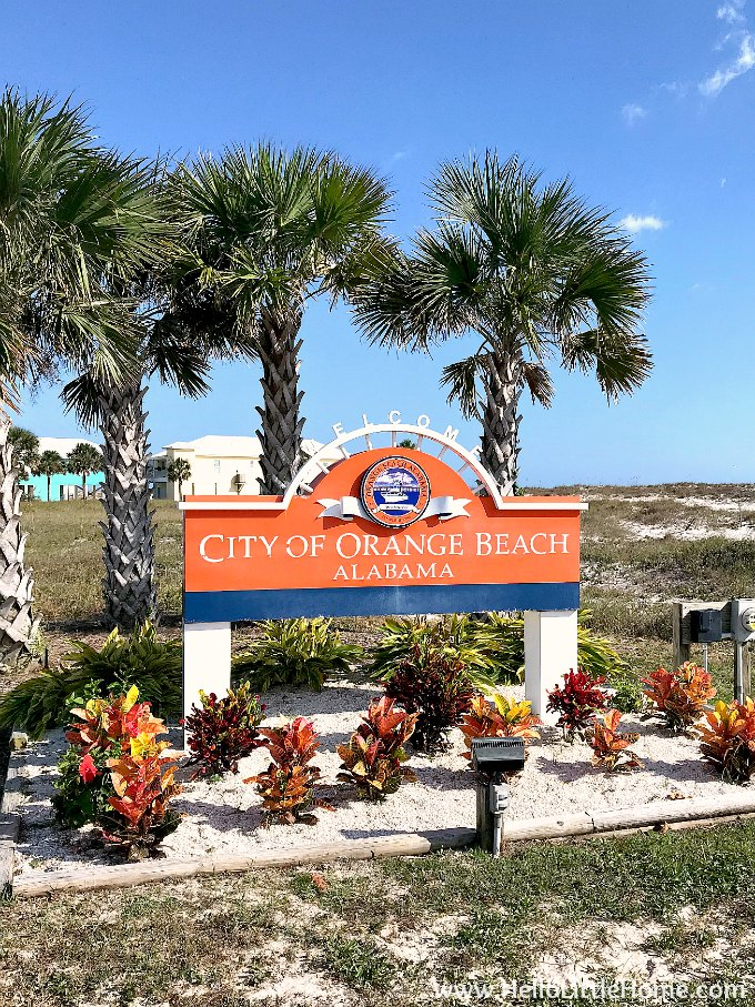 Welcome sign with palm trees in the background as you enter Orange Beach Alabama.