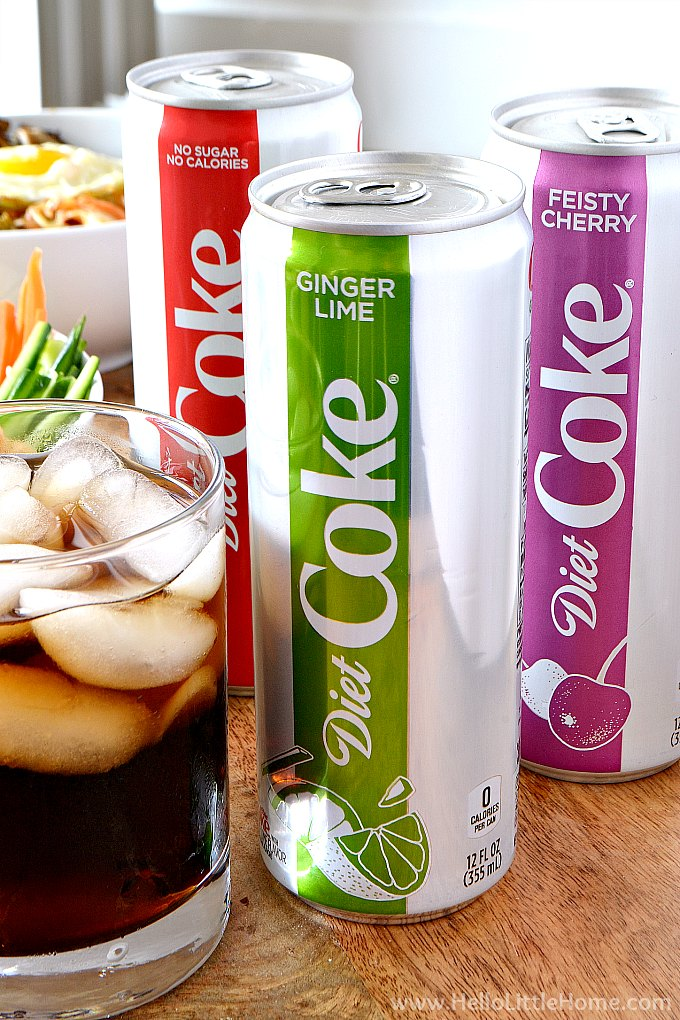 Can of Ginger Lime Diet Coke on a table with more cans and food in background.