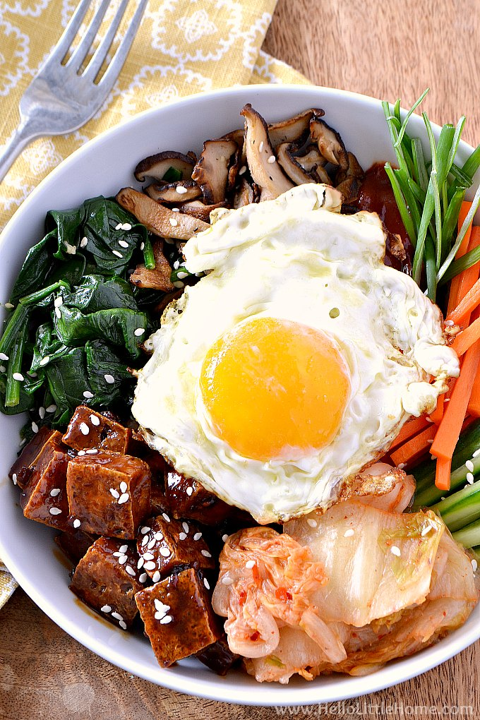 Closeup of a Vegetarian Bibimbap Rice Bowl topped with tofu, spinach, shiitake mushrooms, kimchi, carrots, and a fried egg.