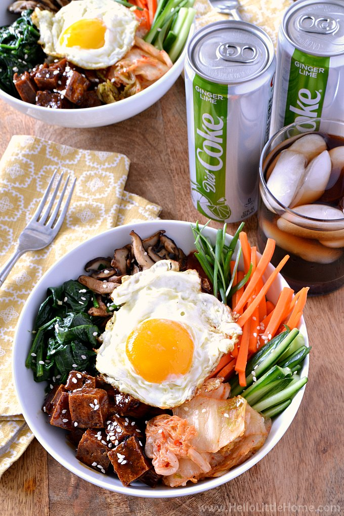 Two bowls of Vegetable Bibimbap on a table with soda, napkins, and forks.