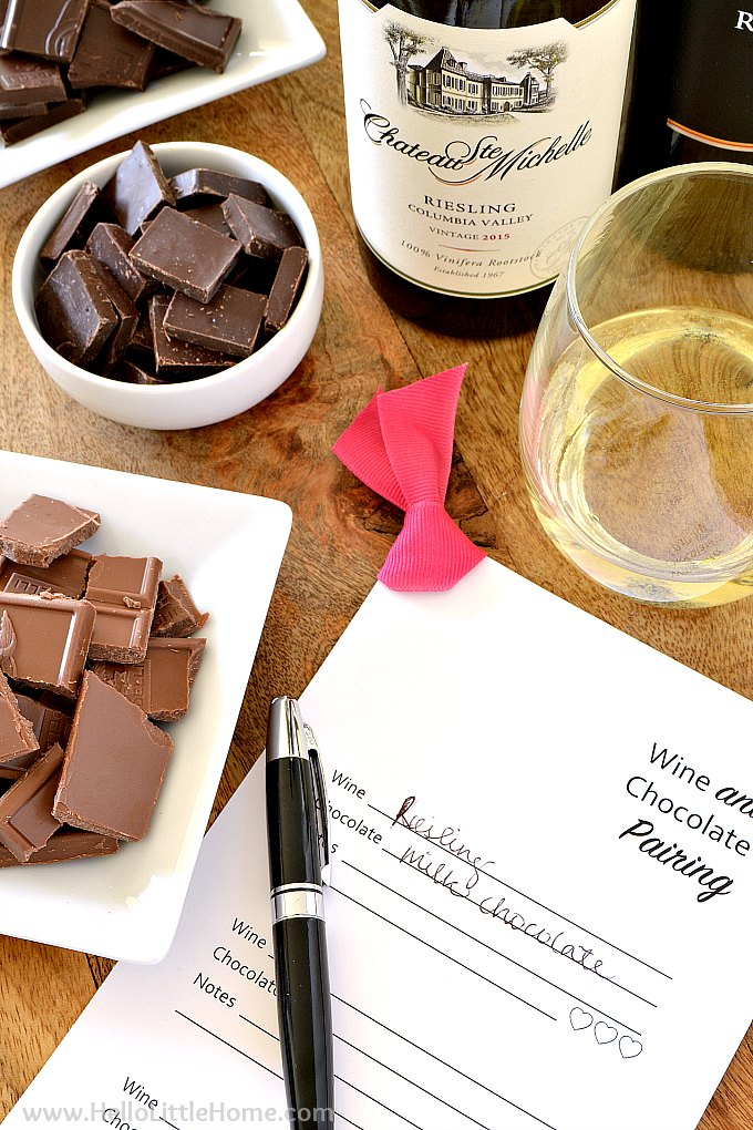 A table with different types of chocolate, a wine and chocolate tasting card, and a glass of white wine.