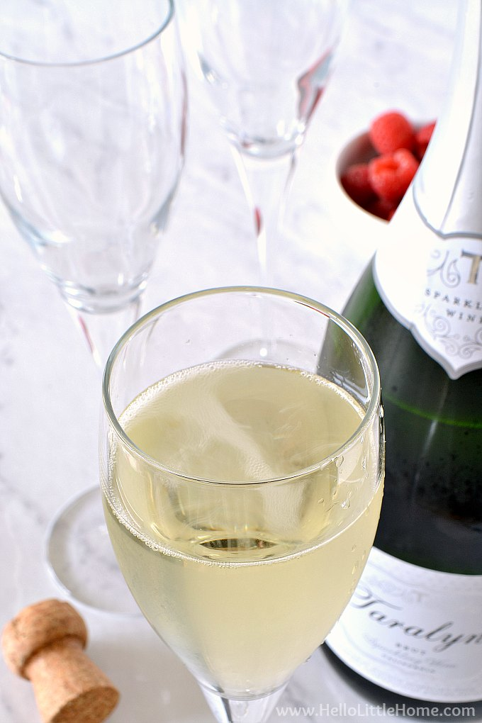 A glass filled with champagne for a Raspberry Mimosa.