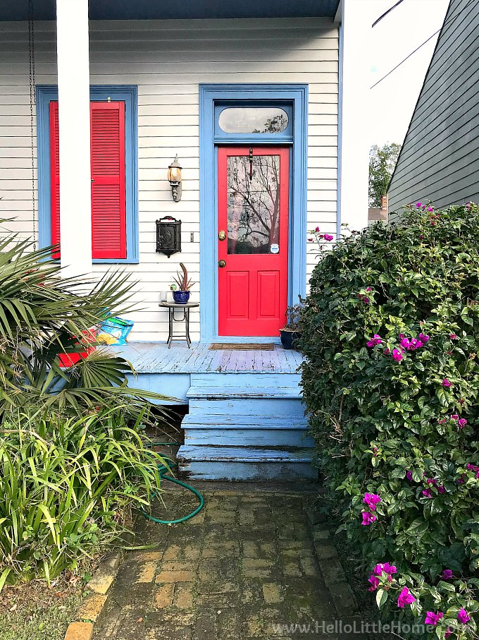 A home in Algiers, New Orleans with a blue porch, red door, and brick path.