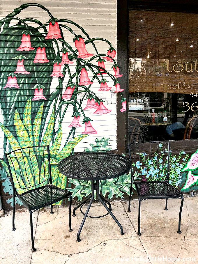 A table and chairs in front of a mural outside the Tout De Suite Cafe in Algiers, New Orleans.