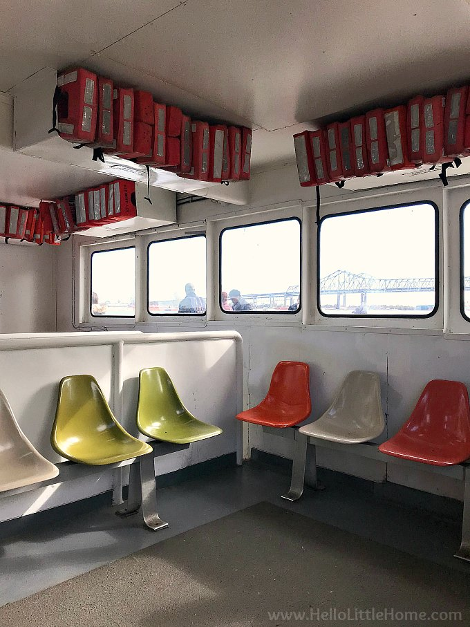 The inside of the Algiers Point Ferry with a view of the Crescent City Connection Bridge through the windows.