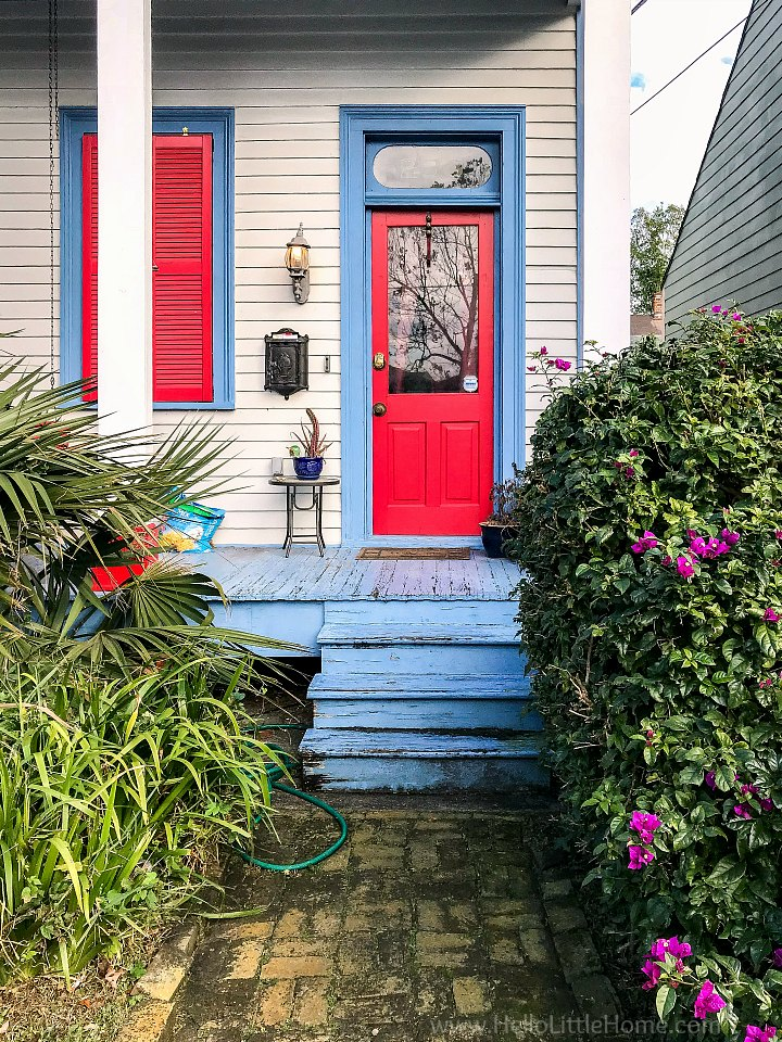 A colorful house with a red door and blue trim.