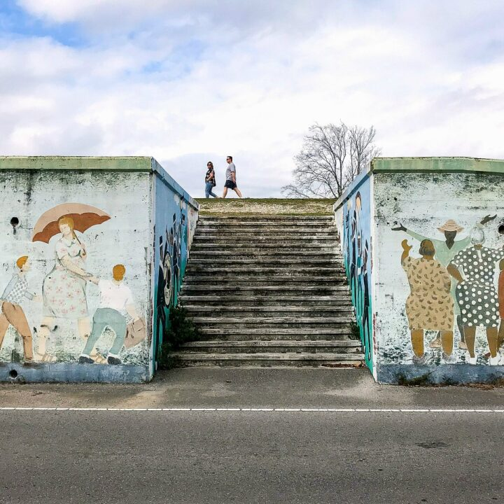Stairs decorated with murals, leading up to the levee path.