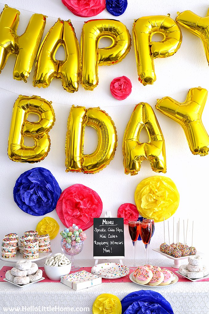 Sprinkles Birthday Party Backdrop with Balloon Banner and DIY Tissue Paper Pom Poms.