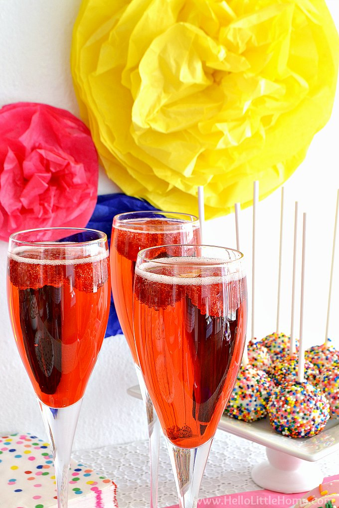 Raspberry Bellini Cocktails with Cake Pops and Tissue Paper Pom Poms in background.