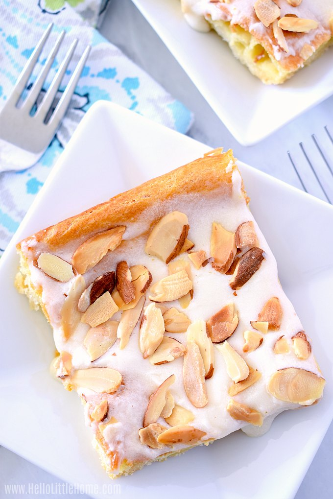 A slice of Danish Puff, and Almond Kringle, topped with a sweet glaze and slice almonds.