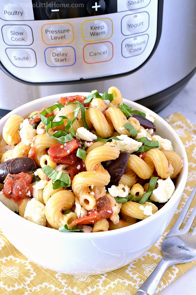 A bowl of vegetarian Instant Pot Pasta in front of an Instant Pot pressure cooker.