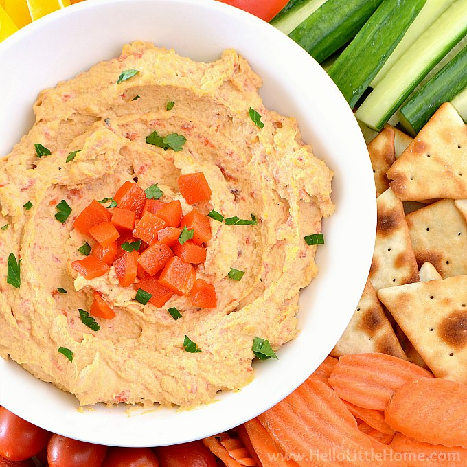 A bowl of roasted red pepper hummus on a veggie tray.