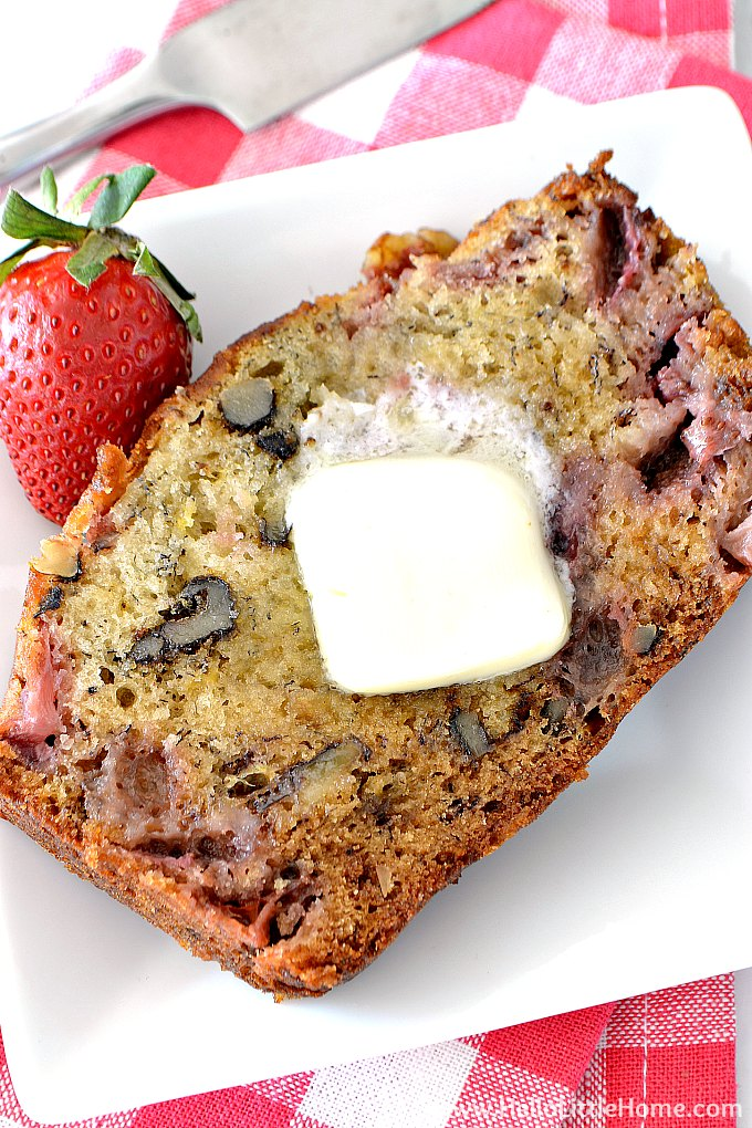 A slice of Strawberry Banana Bread topped with butter.