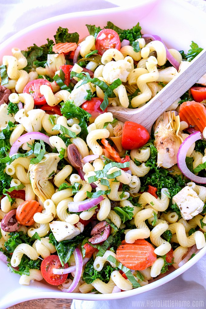 Mixing together a big bowl of Italian Pasta Salad, a cold Antipasto Pasta Salad that vegetarian friendly.