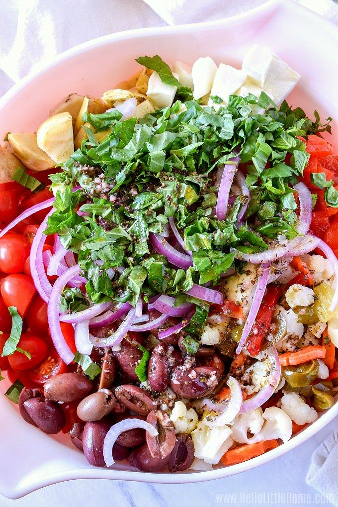 Italian Pasta Salad ingredients (kale, pasta, antipasto, fresh mozzarella + more) in a bowl, ready to be mixed.