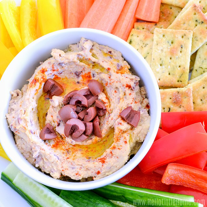 A bowl of Olive Hummus on a tray of veggies.