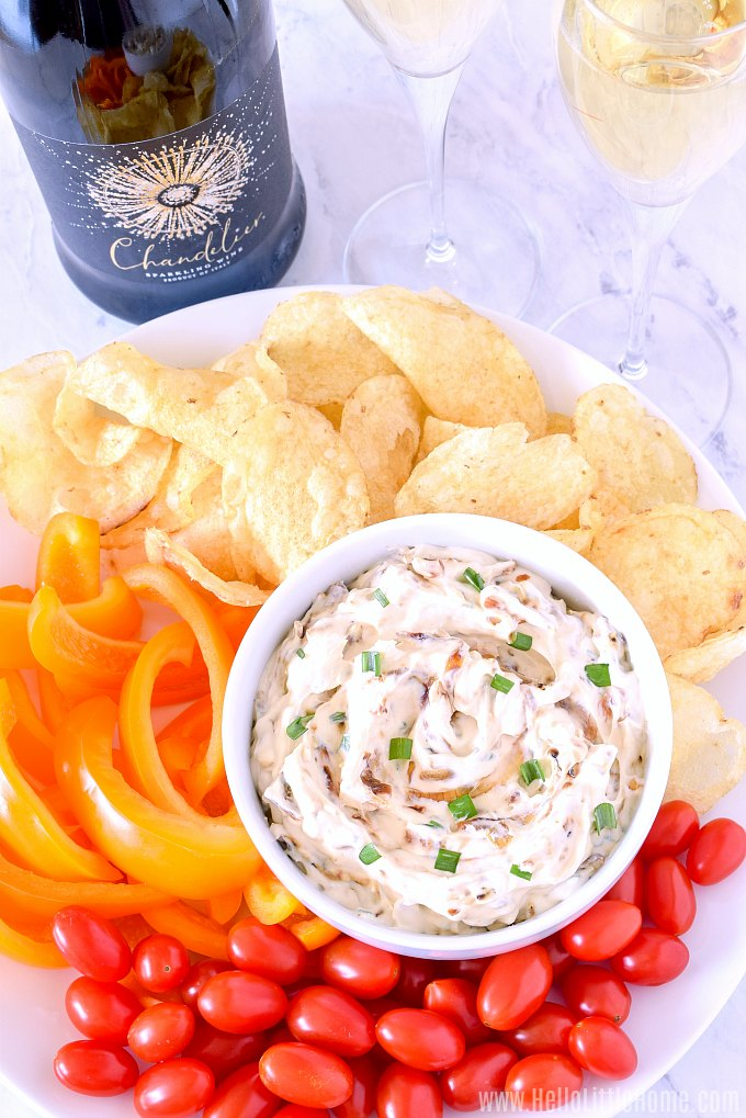 A bowl of creamy Caramelized Onion Dip served with chips, veggies, and sparkling wine.