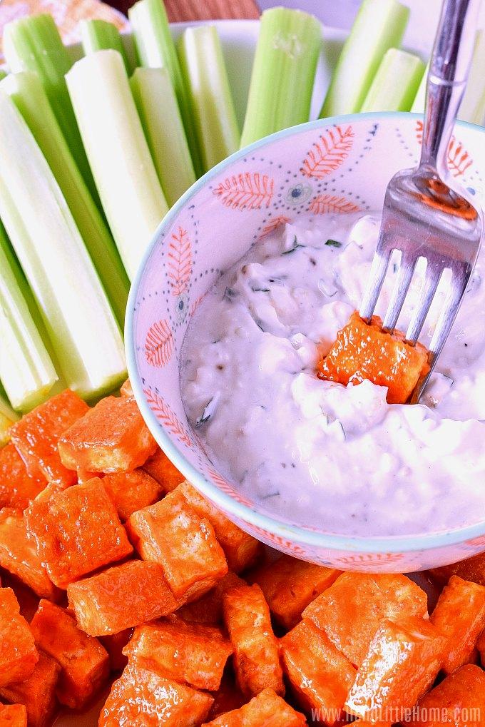 Dipping Buffalo Tofu Bites into Blue Cheese Dip.