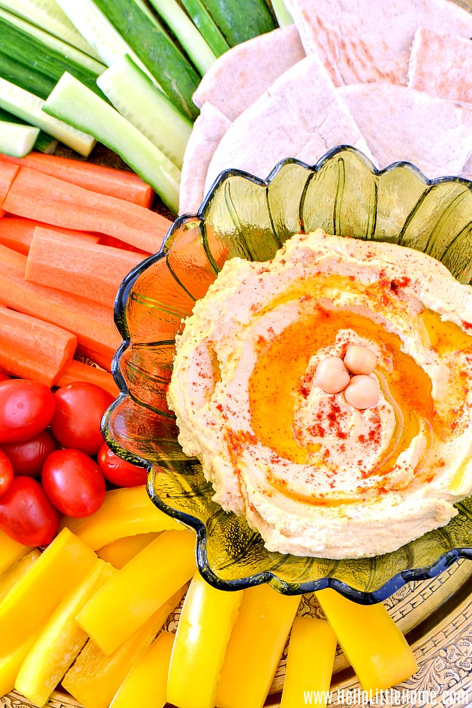 An easy hummus recipe, surrounded by fresh veggies and pita bread.