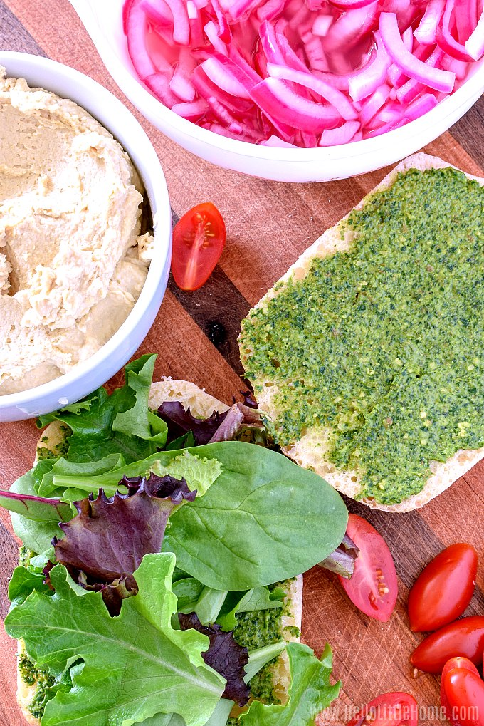 Hummus Sandwich ingredients: pesto, greens, pickled onions, and hummus.