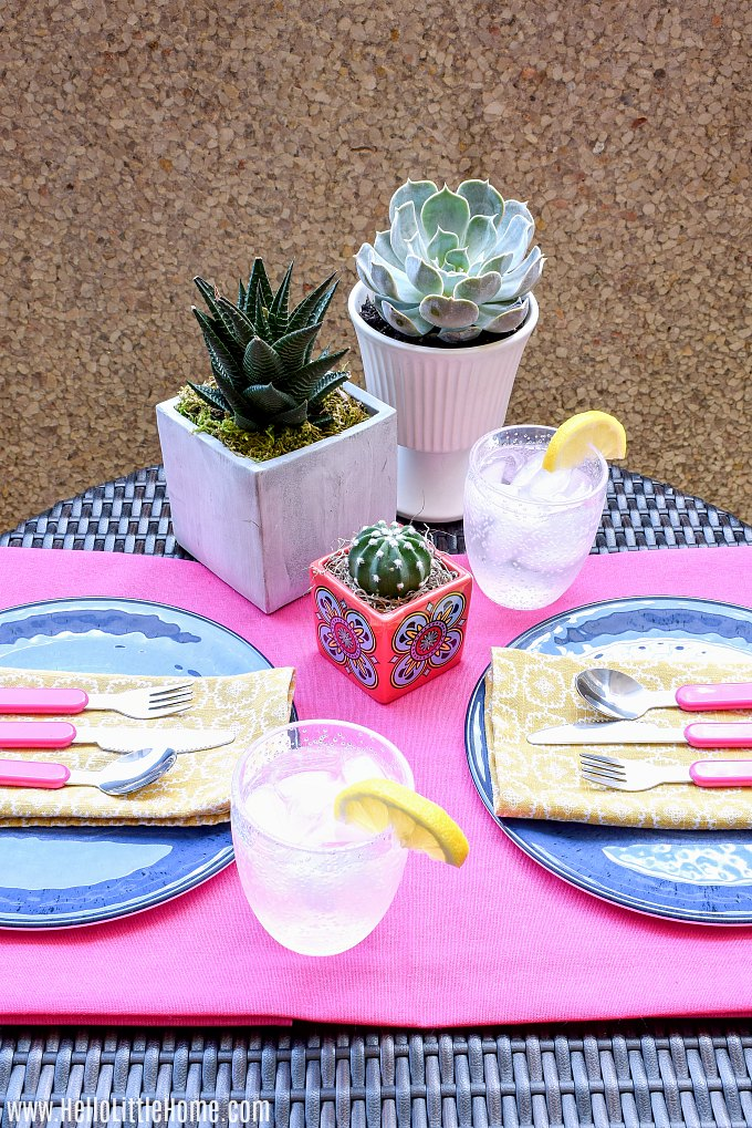 A colorful pink, blue, and yellow table setting for eating outdoors on a small patio.