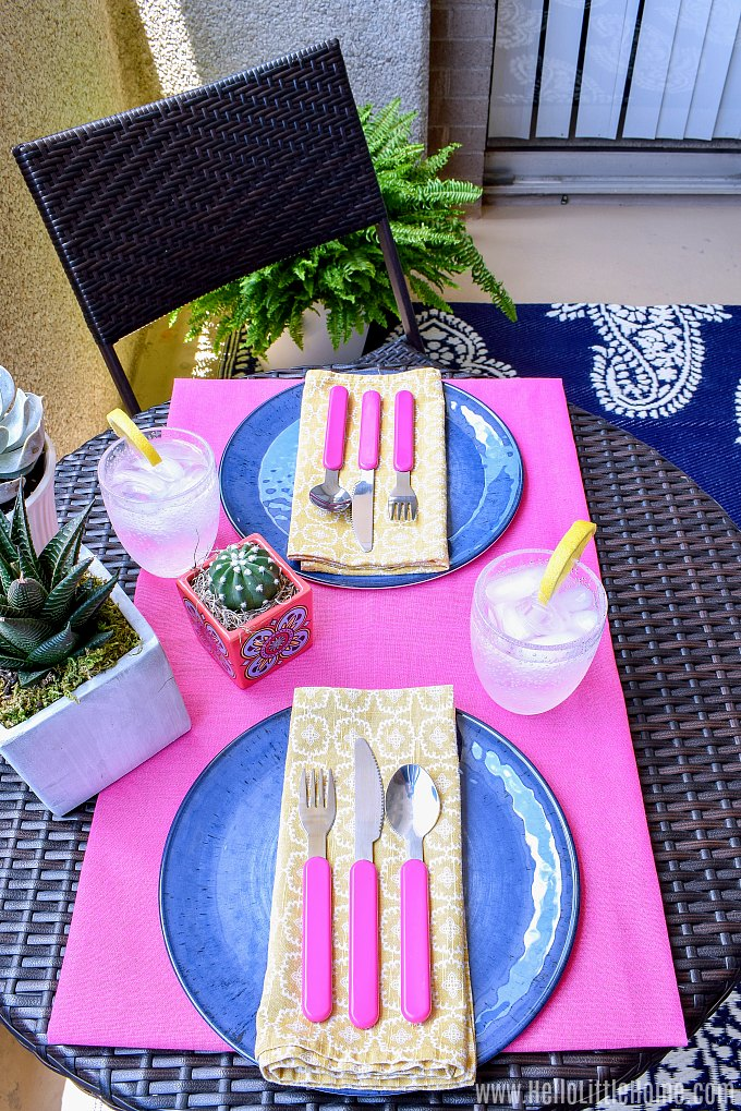 Pink, blue, and yellow table setting for eating outdoors on a small patio.