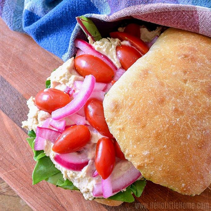 A Hummus Sandwich and a plaid napkin on a cutting board.
