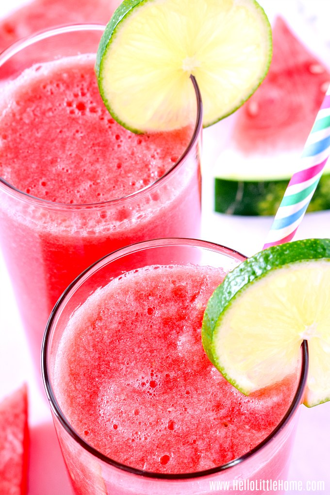 Two glasses of fresh watermelon juice served with lime.