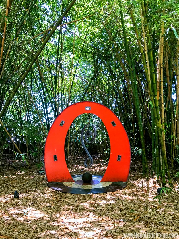 A red sculpture surrounded by trees in the botanical garden.