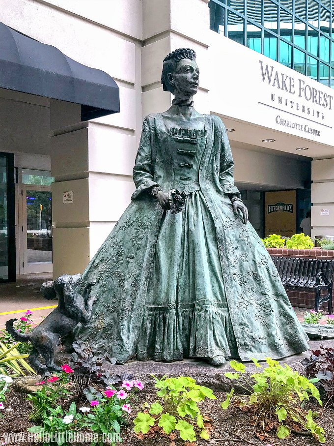 A statue of Queen Charlotte in front of a hotel.